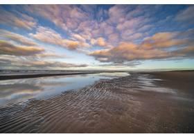 蓝色多云天空下的海边水塘_1017652301