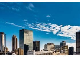 蓝色多云天空下高大的玻璃建筑的低角度拍摄_1086133701