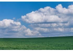 蓬松的云层下美丽的绿色草地_1275051201
