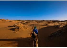 身穿蓝色衬衫的男性在天空晴朗的沙丘中央走_804870101