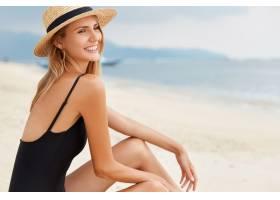 身穿黑色泳衣的时尚美女坐在沙滩上欣赏蔚_954546001