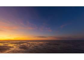 日落时分蓝黄相间的天空下潮湿的海滩海岸的_828170801