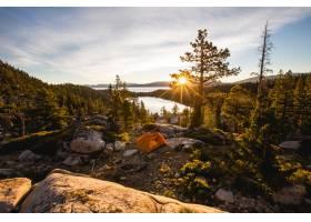 日落时分被树木包围的落基山上橙色帐篷的_803914601