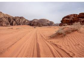 白天多云的天空下满是干草的沙漠上的悬崖和_1040048601