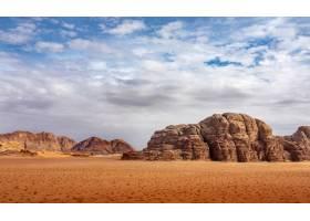 白天多云的天空下满是干草的沙漠上的悬崖和_1244928501