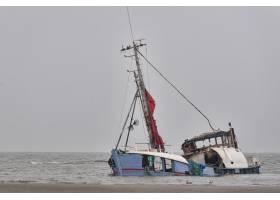 晴朗的天空下在海边沉没的弃船_918510401