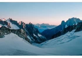 白雪皑皑的小山被群山包围天空呈淡粉色_805470201