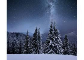 白雪覆盖的山脊上的森林星空中的银河圣_927671701