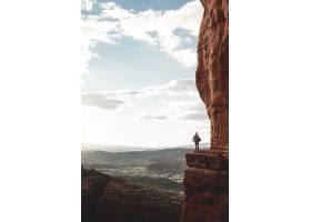 站在晴朗天空下被群山环绕的悬崖边缘的人_792624301