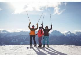 站在积雪覆盖的山上庆祝滑雪者_1123048201