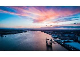 粉色天空下城市里漂浮在水面上的船只的宽阔_1039969301