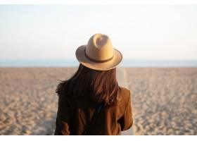 穿着时髦保暖衣服的散发年轻女性走在海岸线_995768401