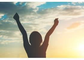 小女孩向自由欢乐时光举手的剪影_365435601