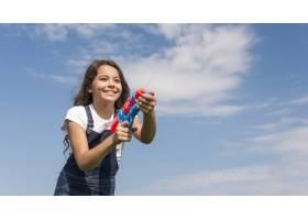 小女孩在外面玩水枪_526363701