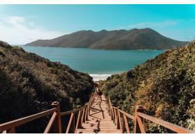 巴西蓝天下绿意盎然的小山和大海环绕的木桥_1040091801