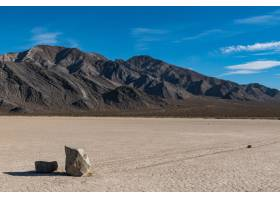 干燥的地面上有两块石头留下的长长痕迹的沙_828150001