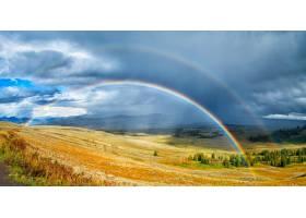 彩虹在多云天空下一片美丽的绿黄相间的田野_1130139901