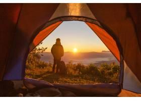 徒步旅行者站在山区橙色帐篷和背包附近的营_435162701