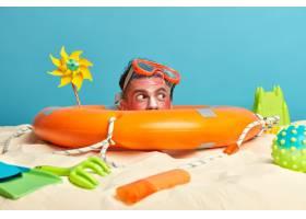 年轻男子头上涂着防晒霜周围环绕着海滩饰_1305611201