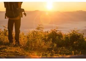 徒步旅行者站在山区橙色帐篷和背包附近的营_435162901