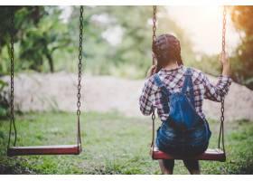 快乐的小女孩在公园里荡秋千_252569401
