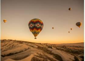 在土耳其卡帕多西亚的日落时分热气球在山_1097907501