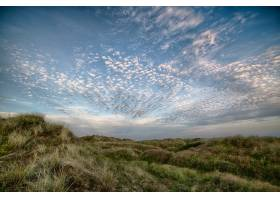 在多云的天空下的小山上美丽地拍下了一片_928253101