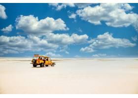 在多云的蓝天下黄色的卡车在沙地上行驶_1054254501