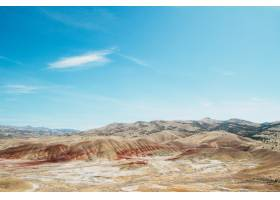 在明亮的天空下高角拍摄荒芜地区的沙丘_1058437601