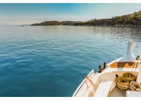 在晴朗的蓝天下一只白色的独木舟在碧绿的_792622301
