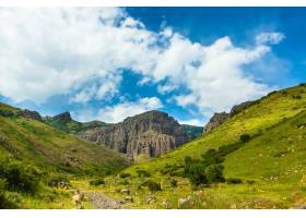 在美丽的多云天空下绿色覆盖的山脉的水平_850715201