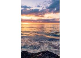 在美丽的日落背景下岩石海滩上令人叹为观_1300581401