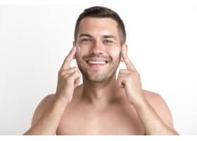 白色背景下赤裸上身的年轻人用面霜按摩的肖_5223647