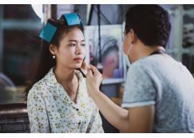 美容院女理发师为可爱的年轻女子站立化妆_5474497