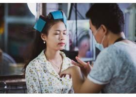 美容院女理发师为可爱的年轻女子站立化妆_5474498