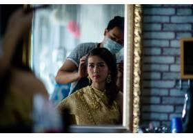美容院女理发师为可爱的年轻女子站立化妆_5474505
