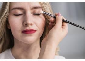 年轻的美女用刷子化妆_4360939