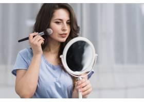 年轻的黑发女子拿着化妆刷照镜子_4351494