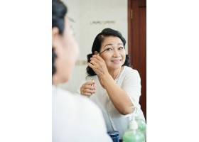 开朗的亚洲老年妇女在镜子前给睫毛涂睫毛膏_5839283