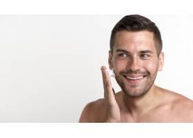 微笑的年轻男子在白色背景下涂抹剃须膏_5245763