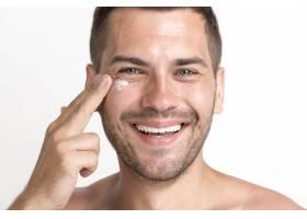 微笑的男子在脸上涂抹面霜的特写_5223643