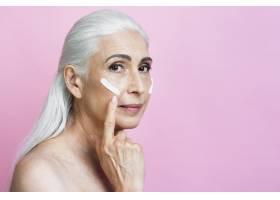 成熟的女人在脸上涂抹面霜_5431136