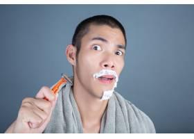 刮胡子的帅哥在灰色的脸上刮胡子_5219039