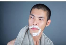 刮胡子的帅哥在灰色的脸上刮胡子_5219041