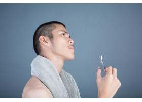 刮胡子的帅哥在灰色的脸上刮胡子_5219045