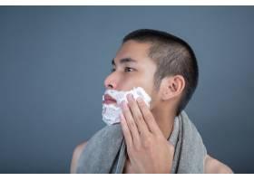 刮胡子的帅哥在灰色的脸上刮胡子_5219048
