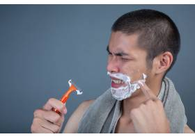 刮胡子的帅哥在灰色的脸上刮胡子_5219050