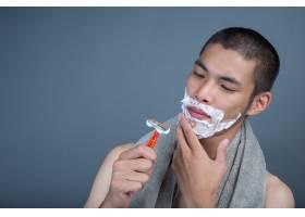 刮胡子的帅哥在灰色的脸上刮胡子_5219051
