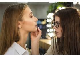 化妆师在嘴唇上涂口红_5863654