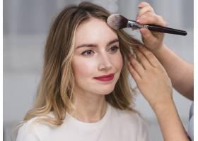 化妆师在女人的额头上打粉_4321269